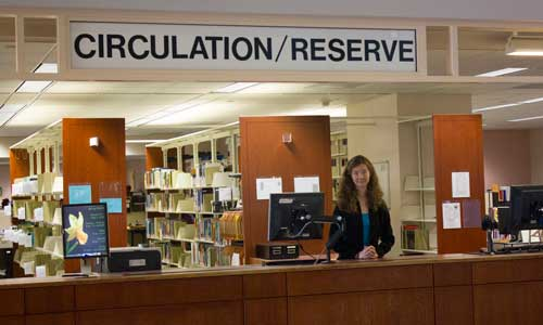 Staff member standing at the Circulation Desk